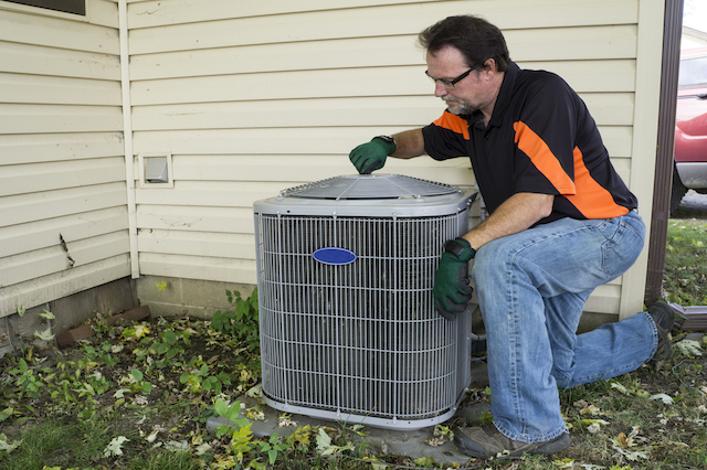 A white middle aged man wearing blue jeans and a black and orange collared shirt is bending down on his knee to inspect an outdoor air conditioning unit
